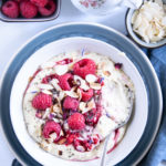 Vanillepudding-Porridge mit warmen Himbeeren in einer weißen Schüssel auf einem blauen Teller im Top View