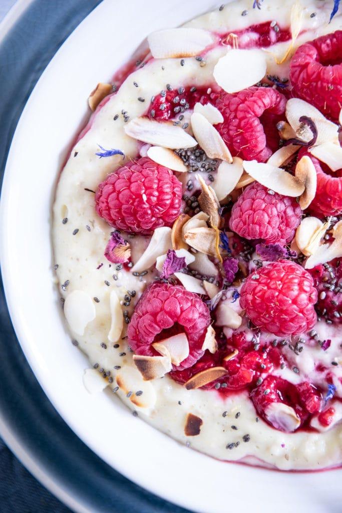 Vanillepudding-Porridge mit warmen Himbeeren in einer weißen Schüsse auf einem blauen Teller im Top View angeschnitten von rechts, mit Himbeeren, Mandelblättchen, Chiasamen und Blüten als Topping