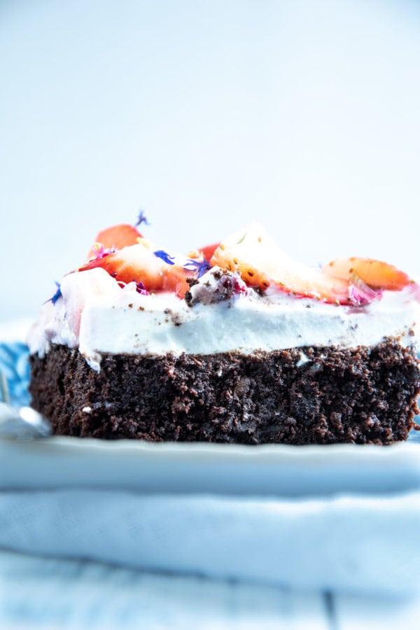 Ein Stück Brownie Style Erdbeerkuchen mit Topfen-Joghurtcreme auf einem dunkelblauen Teller mit Gabel auf Augenhöhe