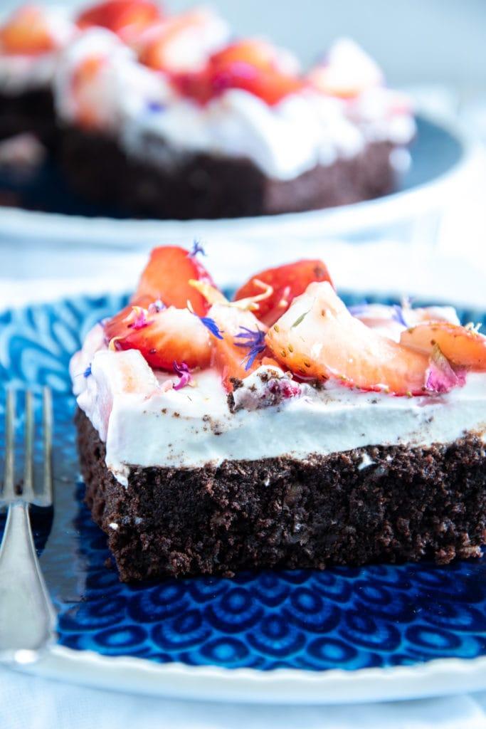 Ein Stück Brownie Style Erdbeerkuchen mit Topfen-Joghurtcreme auf einem dunkelblauen Teller mit Gabel im 45-Grad-Winkel