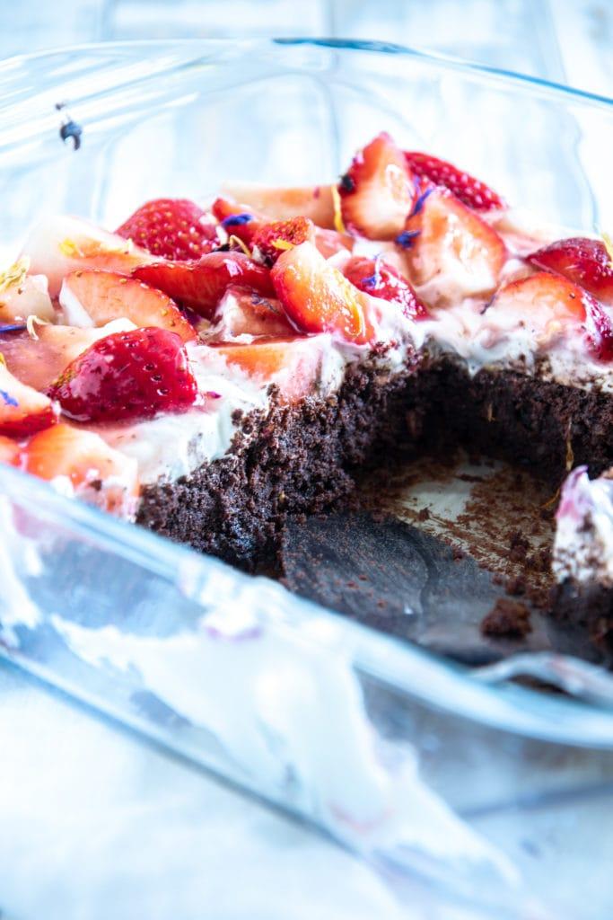 Brownie Style Erdbeerkuchen mit Topfen-Joghurtcreme in einer Glasform auf hellem Untergrund im 45-Grad-Winkel. Einige Stücke aus der Form entnommen.