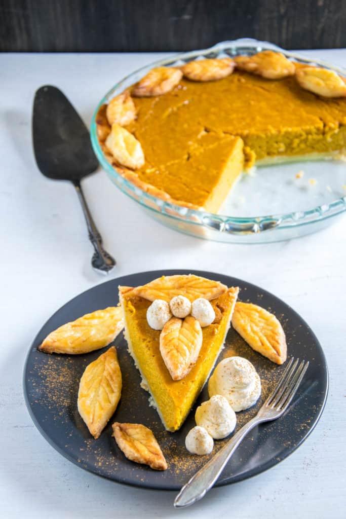 Ein Stück Pumpkin Pie mit Herbstblätter-Deko und Zimt-Sahne