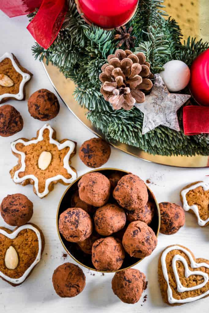 Saftige Gingerbread Energy Bites aus getrockneten Feigen, Pflaumen, Mandeln, Walnüssen, Mandelmus und Lebkuchengewürz in einer goldenen Schale mit Lebkuchen und Adventkranz als Dekoration