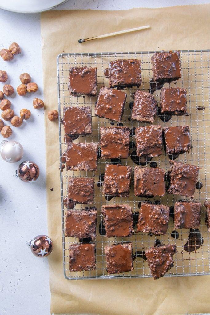 Gesünderes Schokoladenbrot auf einem Pralinengitter zum Trocknen aufgelegt, darunter ein Bogen braunes Backpapier. Dekoriert mit kleinen Christbaumkugeln und Haselnüssen. Aufnahme von oben.