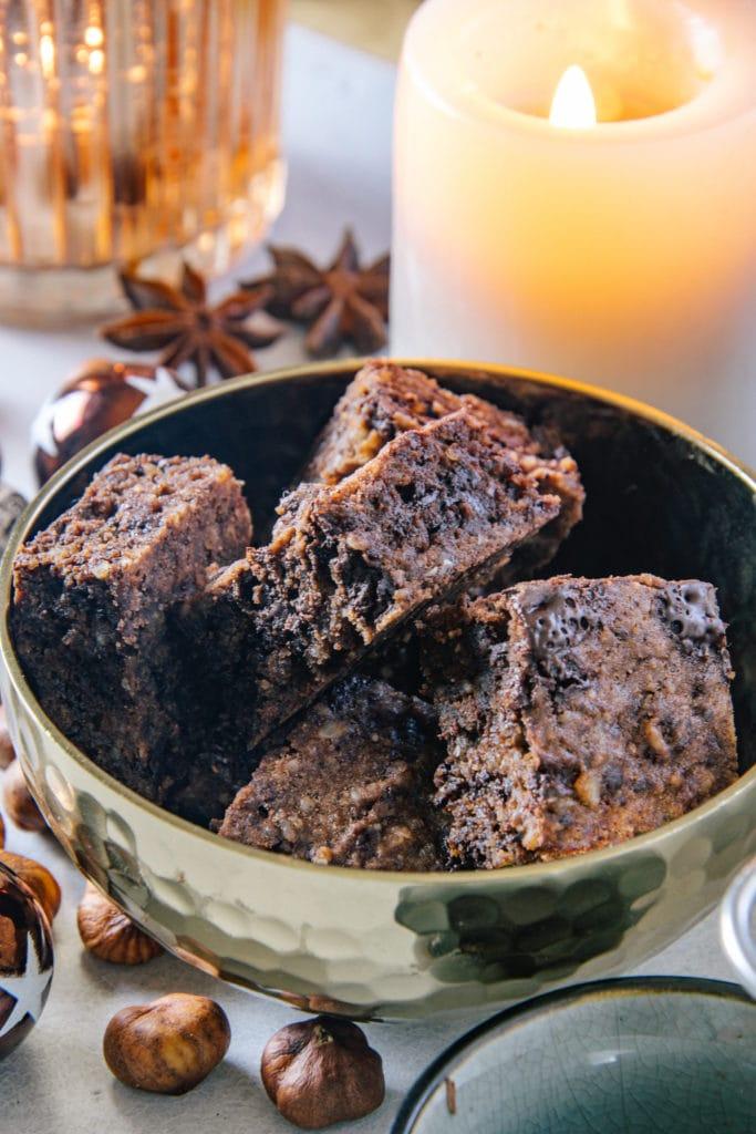 Zuckerfreies Schokoladenbrot in einer goldenen Schüssel im 45-Grad-Winkel fotografiert. Brennende Kerze und Anissterne im Hintergrund.