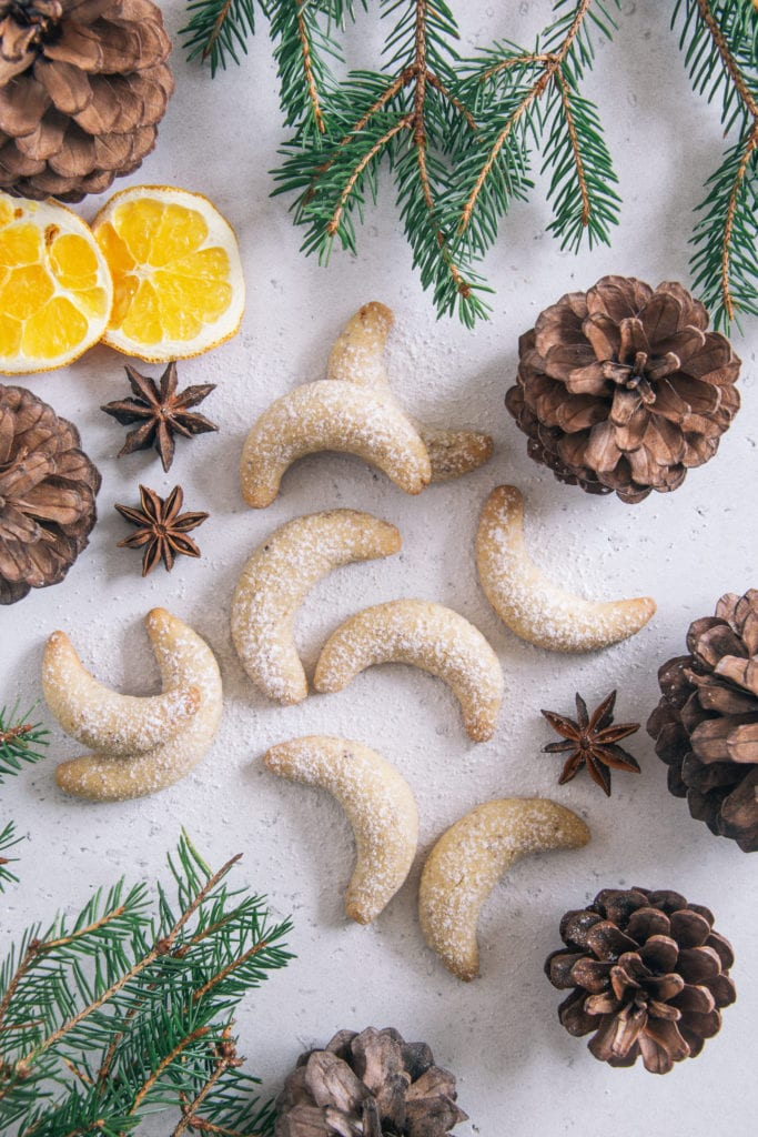 Gesündere Vanillekipferl auf weißem Untergrund dekoriert mit Tannenzweigen, Tannenzapfen, Anissternen und getrockneten Orangenscheiben, bestreut mit Puder-Erythrit. Aufnahme von oben.