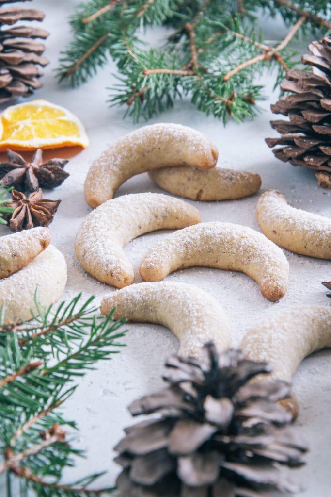 Gesündere Vanillekipferl auf weißem Untergrund dekoriert mit Tannenzweigen, Tannenzapfen, Anissternen und getrockneten Orangenscheiben, bestreut mit Puder-Erythrit. Aufnahme im 45-Grad-Winkel.