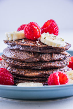 Ein Stapel Double Chocolate Protein-Pancakes garniert mit Bananenscheiben und Himbeeren. Fotografiert auf Augenhöhe.