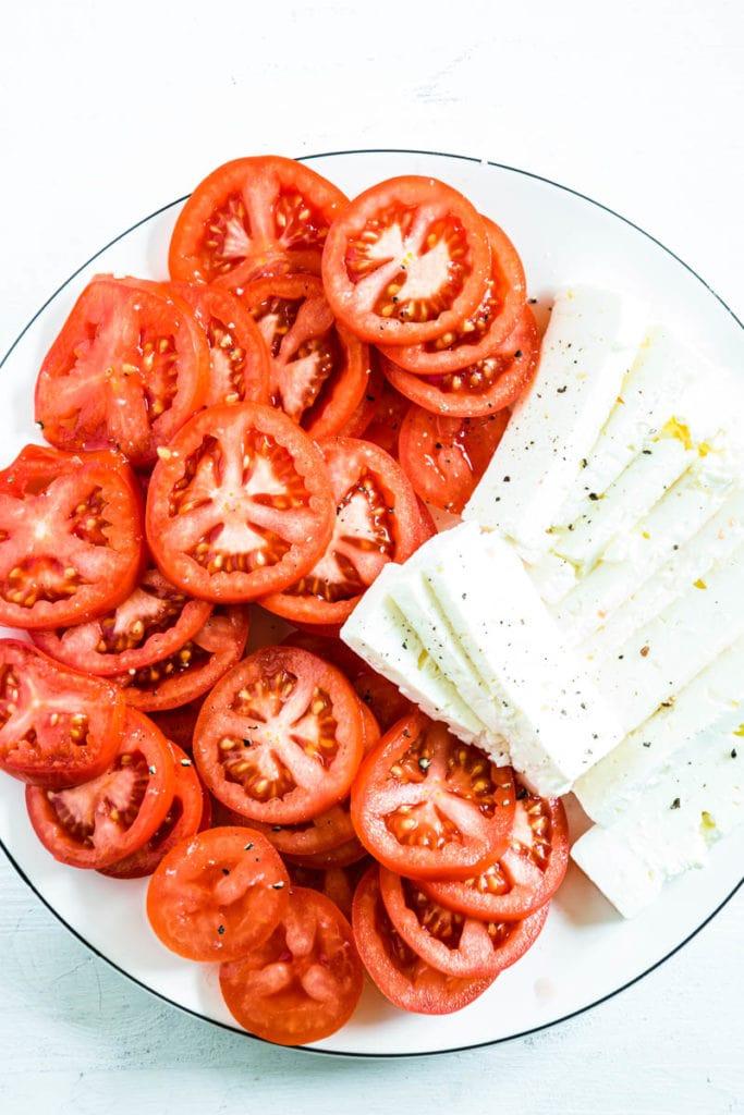 Tomatenscheiben und Feta für Polenta-Spinatgratin mit Feta