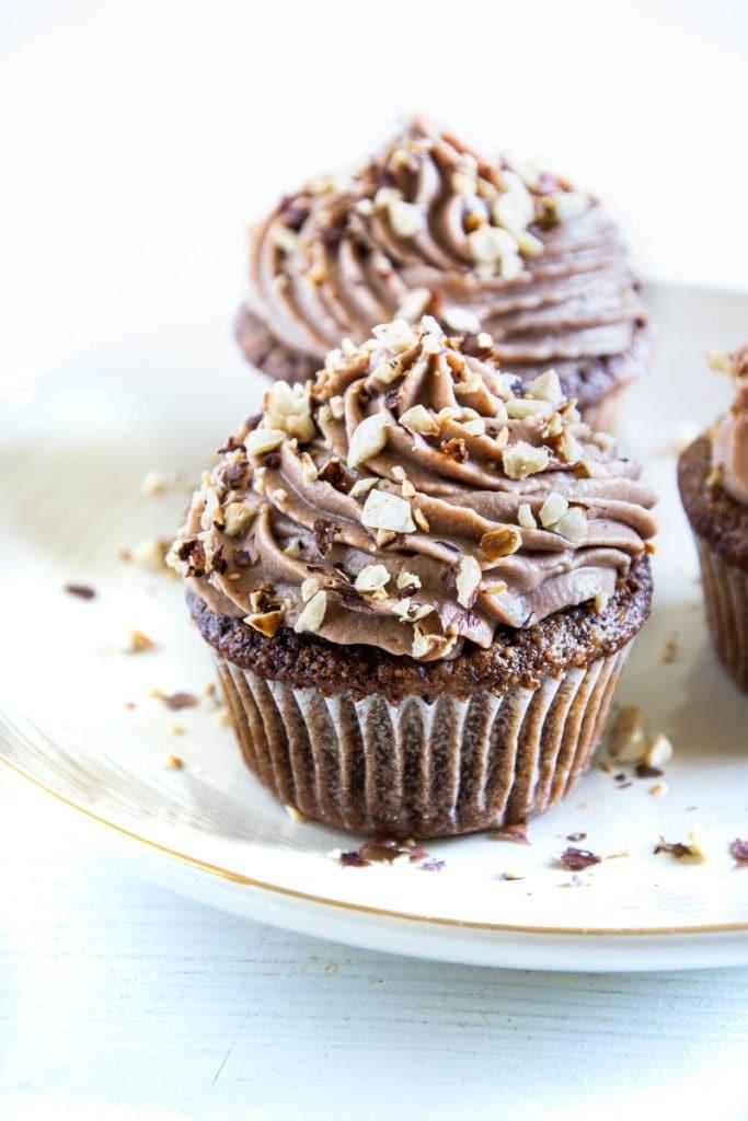 Zwei Haselnuss-Nougat-Cupcakes hintereinander auf einem hellen Teller
