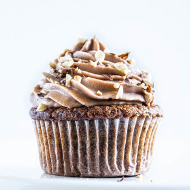 Ein Haselnuss-Nougat-Cupcake in Frontansicht auf einer Kuchenplatte