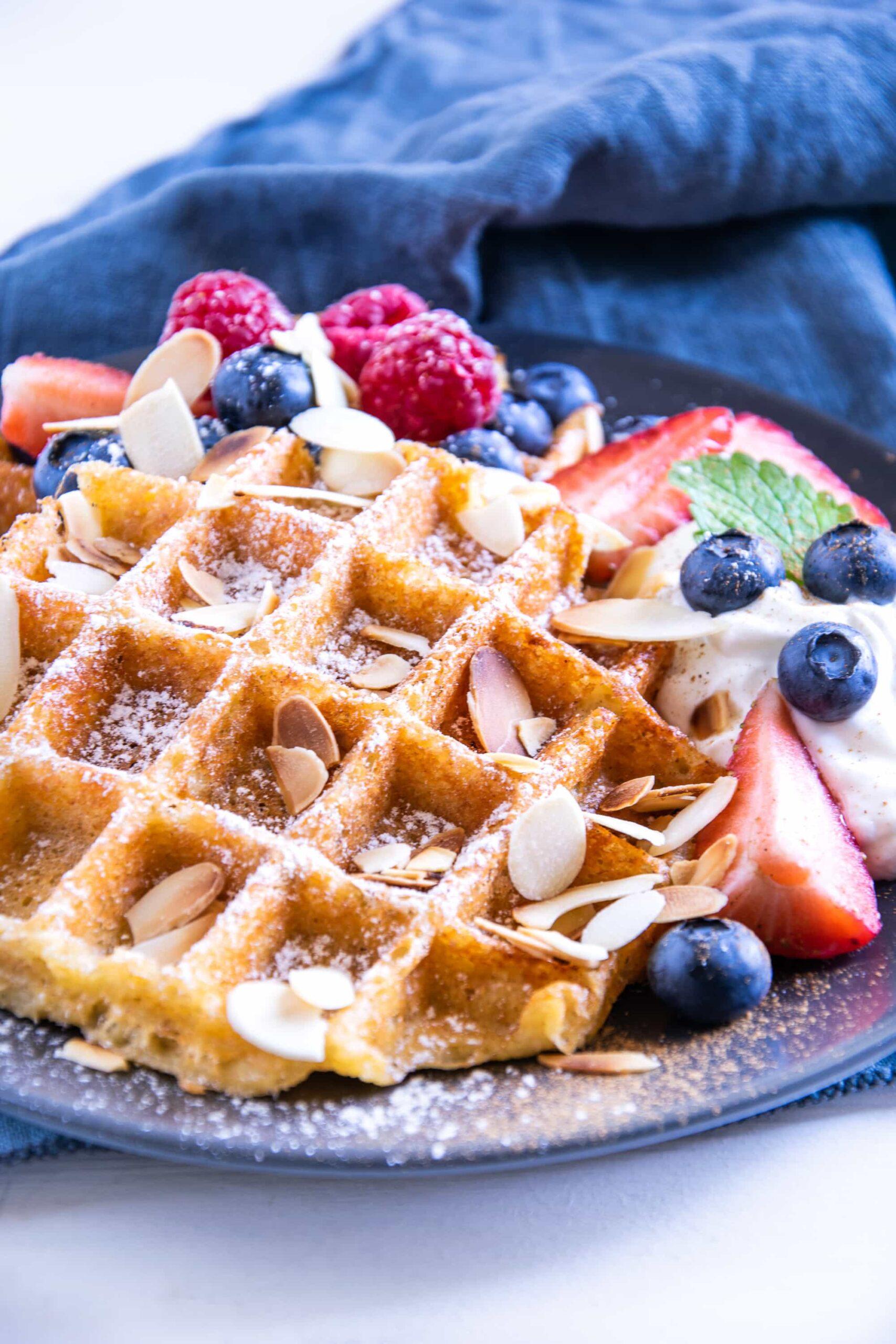 Knusprige Keto Zimt-Chaffles mit griechischem Sahnejoghurt, Beeren, gerösteten Mandelblättchen, Minze- und Melisseblättern auf einem schwarzen Teller mit einem dunkelblauen Leinentuch darunter. Aufnahme im 45°-Winkel.
