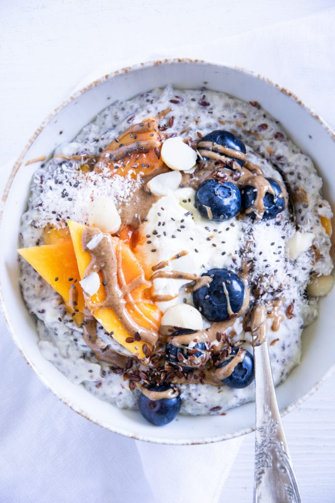 Noatmeal mit Kokos und Papaya in einer hellen Schüssel auf weißem Untergrund. Garniert mit Heidelbeeren, Papayaspalten, Kokosflocken und Mandelmus. Ein Löffel in der Schüssel. Top View.