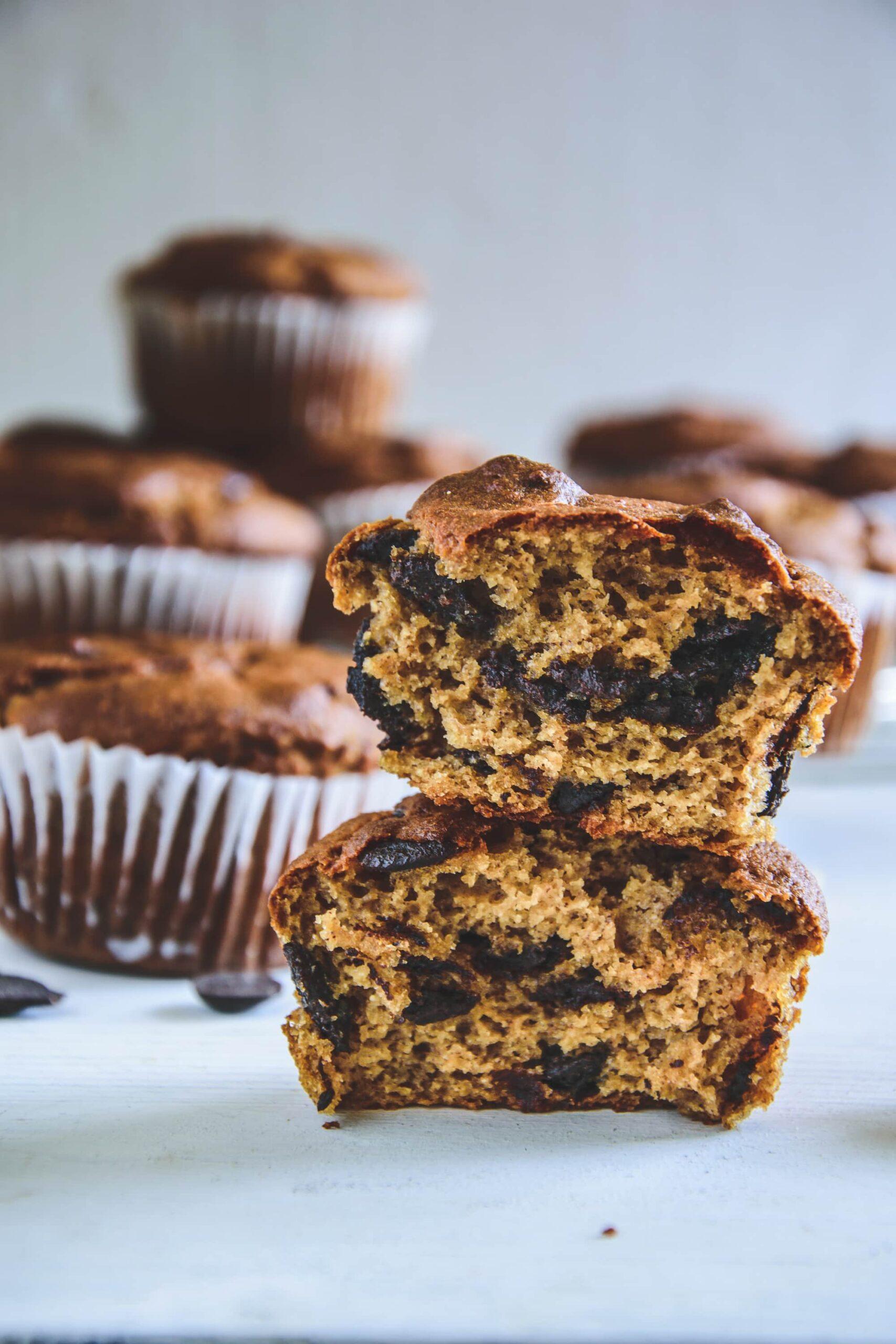 Ein halbierter Peanut Chocolate Chip Muffins mit der Textur im Fokus und weiteren Muffins im Hintergrund. Fotografiert auf Augenhöhe.