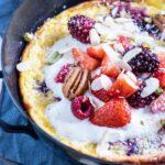 Süßes Keto-Omelette in einer schwarzen Gusseisen-Servierpfanne getoppt mit Mascarpone-Joghurtcreme, Beeren und Nüssen. Blaues Leinentuch und Top View.