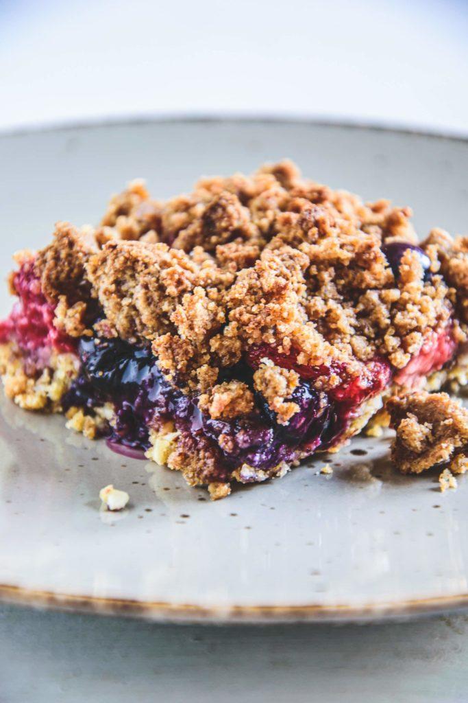 Ein Stück gesunder, zuckerfreier Beeren-Streuselkuchen auf einem grauen Teller. Ansicht im 45-Grad-Winkel. Sehr knusprige Textur.