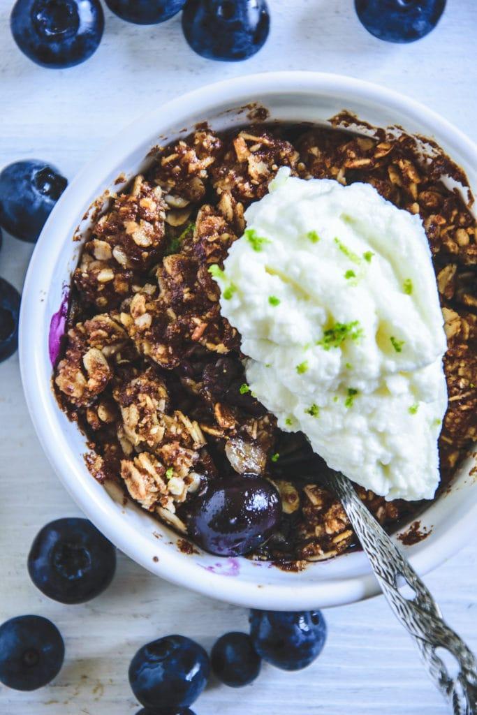 Blueberry Crumble mit Limetten-Quark in einer kleinen, weißen Portionsform mit Heidelbeeren rundherum. Top View.