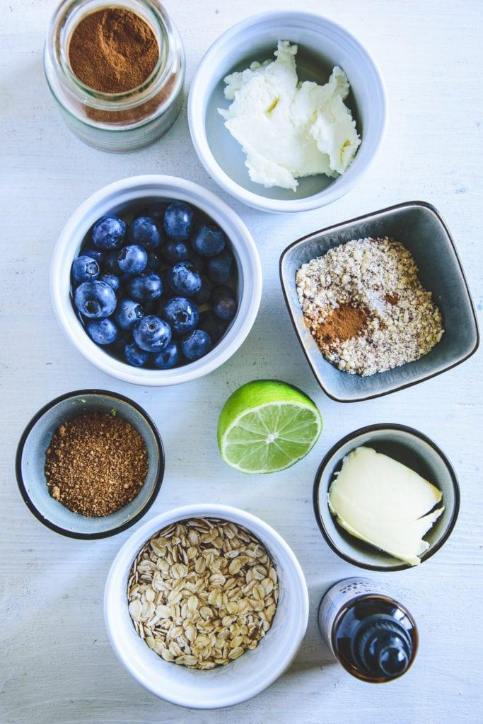 Zutaten für Blueberry Crumble mit Limetten-Quark in diversen kleinen Gefäßen auf hellem Untergrund. Top View.