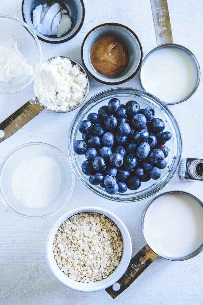 Zutaten für Heidelbeer-Kokos-Porridge in diversen kleinen Gefäßen auf weißem Untergrund. Top View.