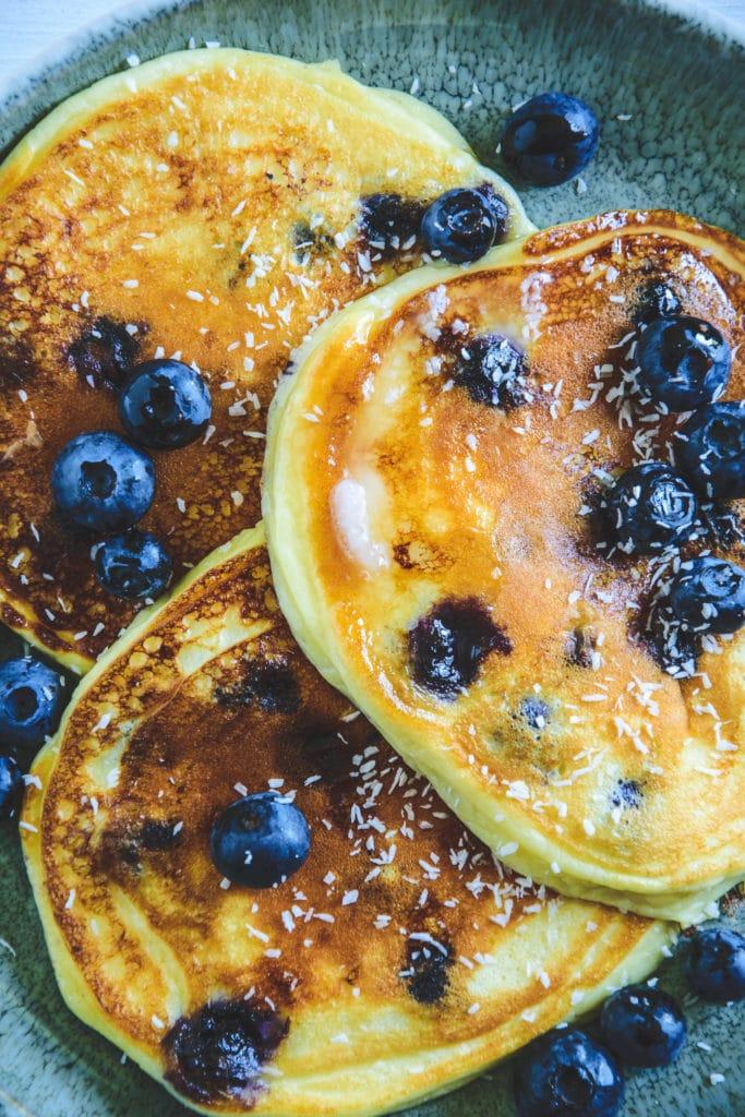 Heidelbeer-Topfen-Pancakes mit Gabel auf dunkeltürkisem Teller. Garniert mit Heidelbeeren. Top View.
