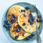 Heidelbeer-Topfen-Pancakes mit Gabel auf dunkeltürkisem Teller. Garniert mit Heidelbeeren. Weißer Untergrund. Top View.