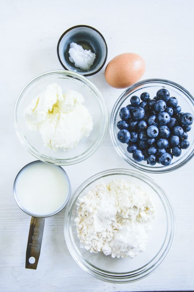 Zutaten für Heidelbeer-Topfen-Pancakes in diversen kleinen Gefäßen auf weißem Untergrund. Top View.