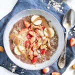 Cremiger Schoko-Mandel-Porridge getoppt mit Bananenscheiben, Erdbeeren, Mandeln und Mandelmus. In einer blaugrauen Schüssel mit Löffel darin, auf einem blauen Leinentuch. Top View.