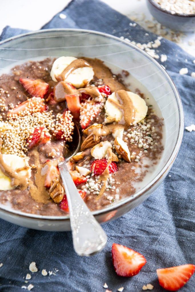Schoko-Mandel-Porridge getoppt mit Bananenscheiben, Erdbeeren, Mandeln und Mandelmus. In einer blaugrauen Schüssel mit Löffel darin. 45-Grad-Winkel