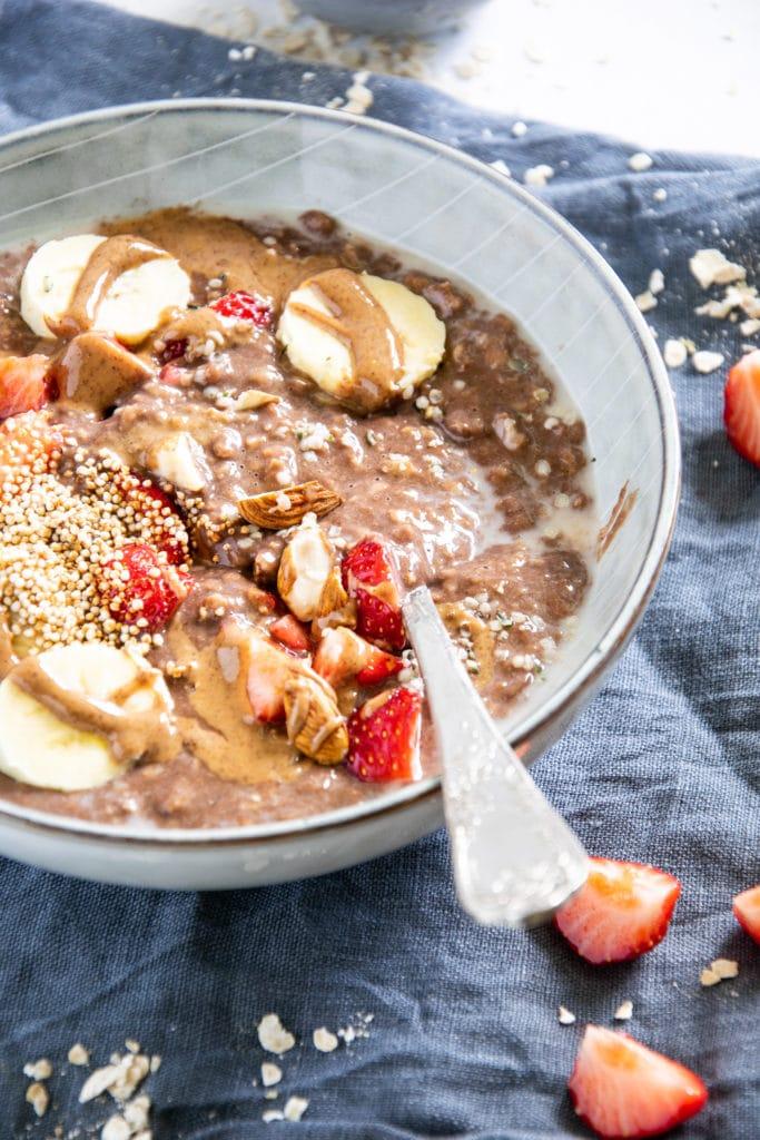 Schoko-Mandel-Porridge getoppt mit Bananenscheiben, Erdbeeren, Mandeln und Mandelmus. In einer blaugrauen Schüssel mit Löffel darin. 45-Grad-Winkel.