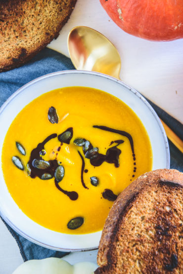 Sehr gelb-orange, cremige Kürbissuppe mit Kernöl marmoriert und mit Kürbiskernen bestreut in einer hellen, grau-blauen Schüssel mit einer Scheibe geröstetem Brot am Rand