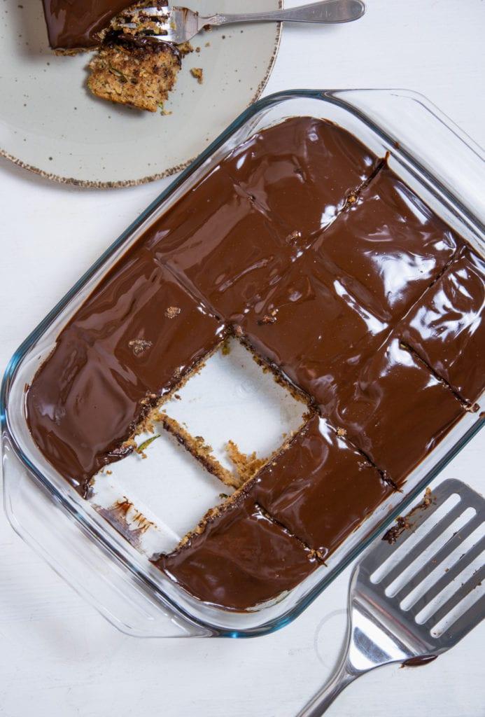 Saftiger gesunder Zucchinikuchen mit weicher Schokoladenglasur in einer Glasform. Aufnahme im Top View.