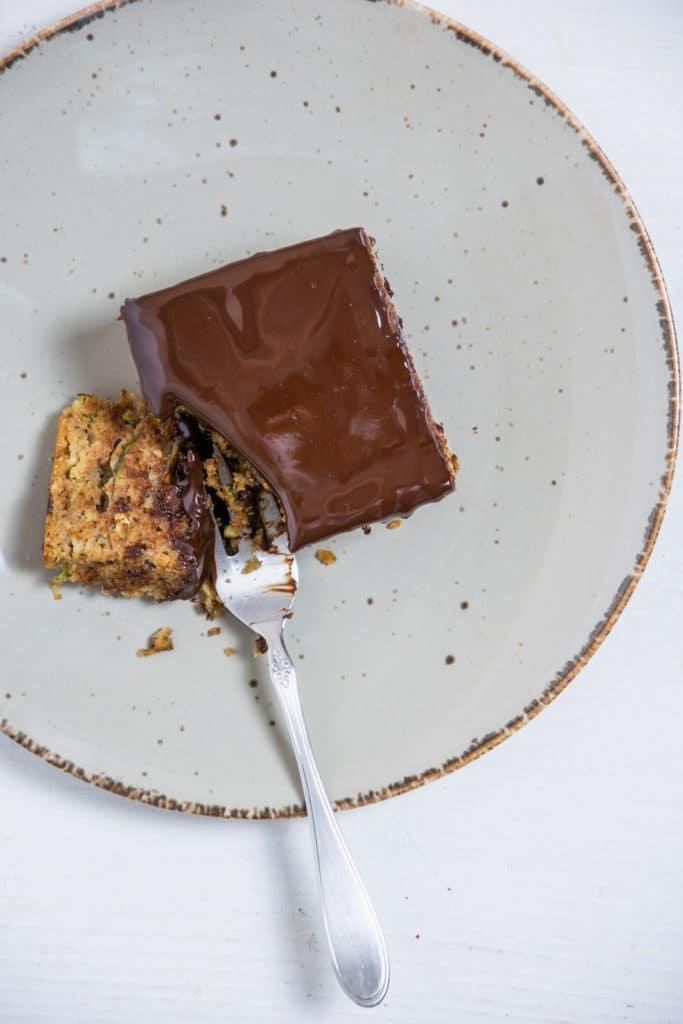 Eine Gabel hat ein Stück saftigen gesunden Zucchinikuchen mit weicher Schokoladenglasur abgestochen. Aufnahme im Top View.