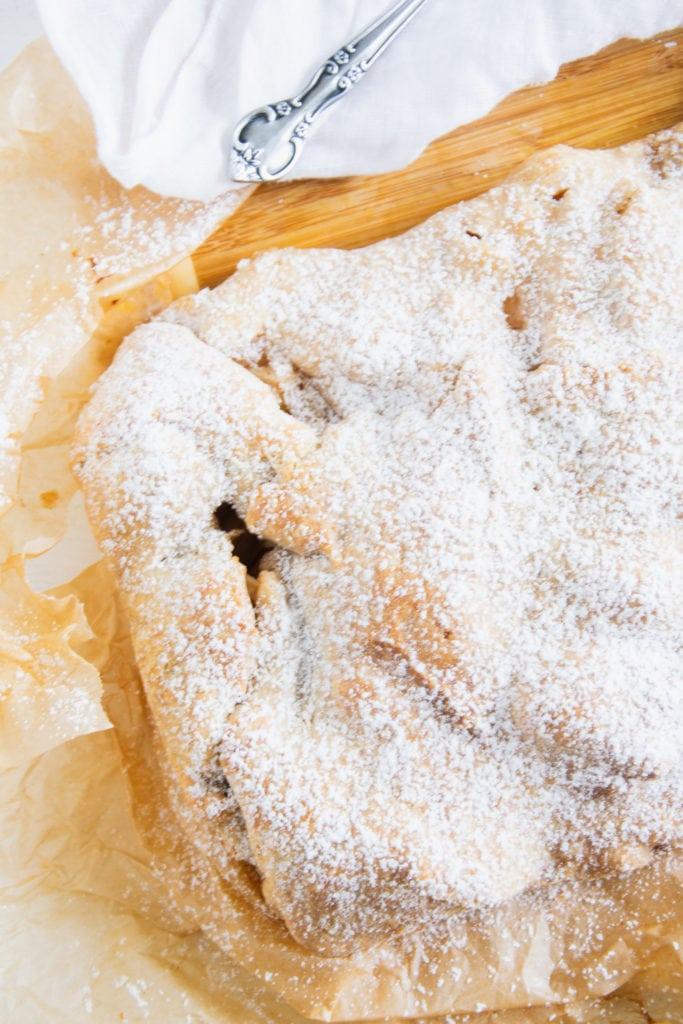 Gesunde Apfelschlangerl mit Puder-Erythrit bestreut auf braunem Backpapier und einem großen Holzbrett. Apfelschlangerl von rechts angeschnitten, geht nach links unten ins Bild. Aufnahme im Top View.