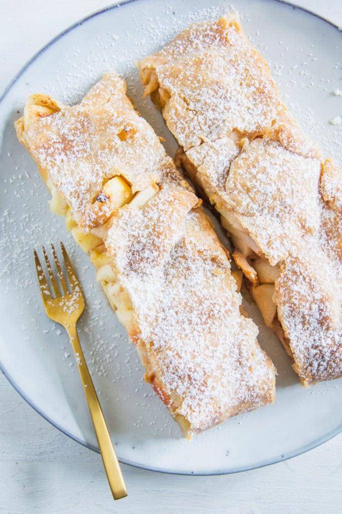 Zwei Stücke Apfelschlangerl auf einem graublauen Teller mit einer goldenen Kuchengabel. Aufnahme im Top View