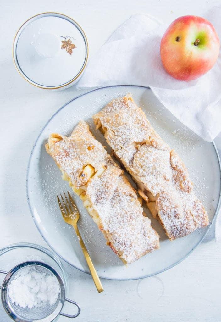 Zwei Stücke Apfelschlangerl auf einem graublauen Teller mit einer goldenen Kuchengabel. Weißter Untergrund mit weißem Tuch, Apfel und Zuckerdose als Dekoration. Aufnahme im Top View.