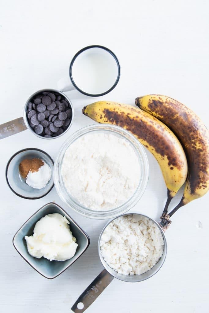Zutaten für Banane-Schoko-Protein-Tassenkuchen in Schüssel auf weißem Untergrund. Flatlay.