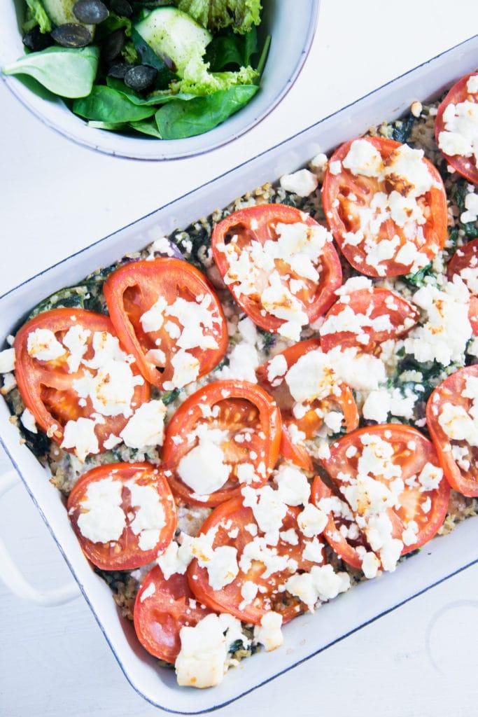 Gesunder Bulgur-Spinatauflauf mit Kichererbsen, Tomaten und Feta in einer weißen Emaille-Auflaufform. Aufnahme von oben auf weißem Untergrund. Schüssel mit Salat neben der Auflaufform.