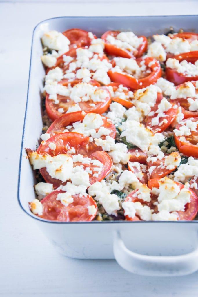 Gesunder Bulgur-Spinatauflauf mit Kichererbsen, Tomaten und Feta im 45-Grad-Winkel fotografiert.