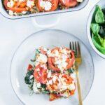 Ein Stück Gesunder Bulgur-Spinatauflauf mit Kichererbsen, Tomaten und Feta auf einem graublauen Teller mit einer goldenen Gabel und einer Salatschüssel daneben auf weißem Untergrund. Aufnahme im Top View.