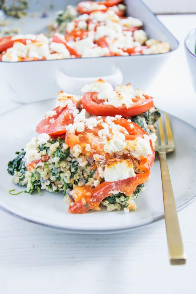 Ein Stück Gesunder Bulgur-Spinatauflauf mit Kichererbsen, Tomaten und Feta auf einem graublauen Teller mit einer goldenen Gabel daneben. Aufnahme im 45-Grad-Winkel.