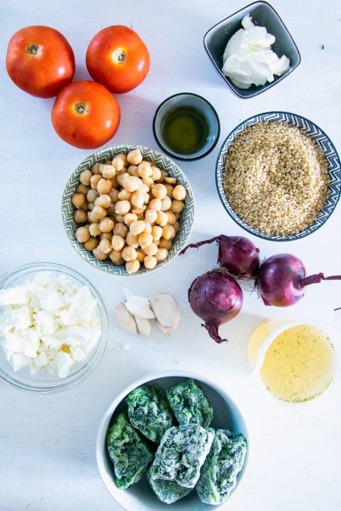 Zutaten für Bulgur-Spinatauflauf mit Kichererbsen, Tomaten und Feta auf weißem Untergrund. Flatlay.
