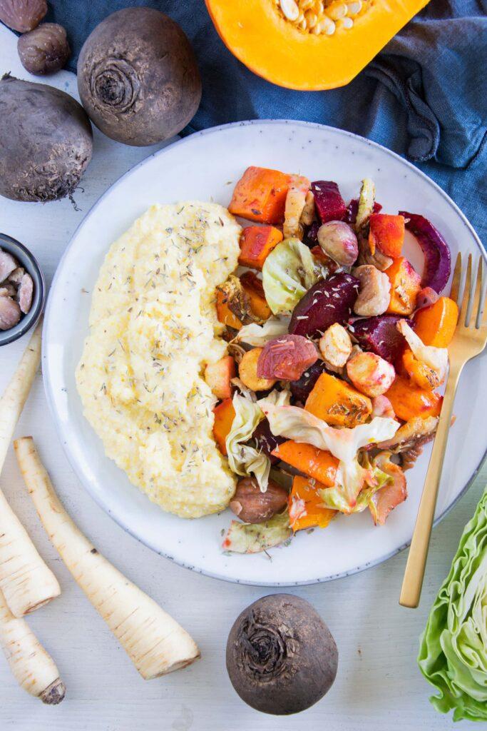 Herbst-Ofengemüse mit Polenta auf einem graublauen Teller mit goldener Gabel. Aufnahme von oben.