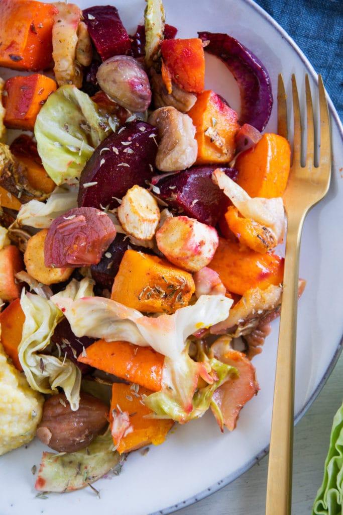 Nahaufnahme im Top View von Herbst-Ofengemüse mit goldener Gabel auf graublauem Teller.