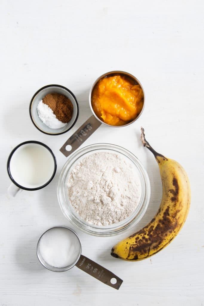 Zutaten für vegane Kürbis-Pancakes in Schüsseln auf weißem Untergrund. Flatlay.