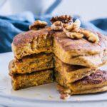Drei vegane Kürbis-Pancakes gestapelt und angeschnitten mit Walnüssen und Ahornsirup. Aufnahme auf Augenhöhe.