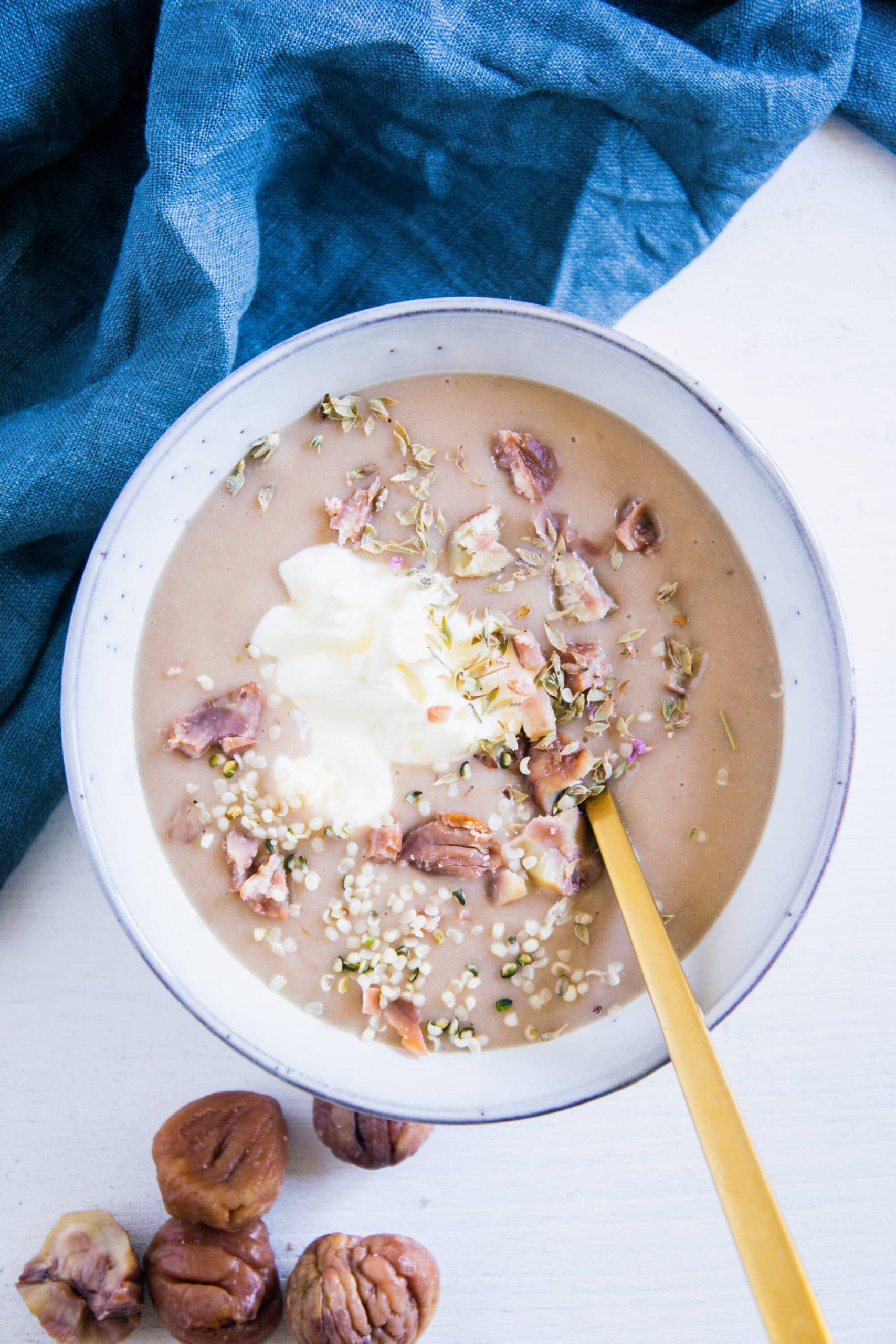 Maroni-Kartoffelsuppe in einer graublauen Schüssel mit einem goldenen Löffel. Garniert mit Maronistücken, Hanfsamen und Crème fraîche. Aufnahme von oben.