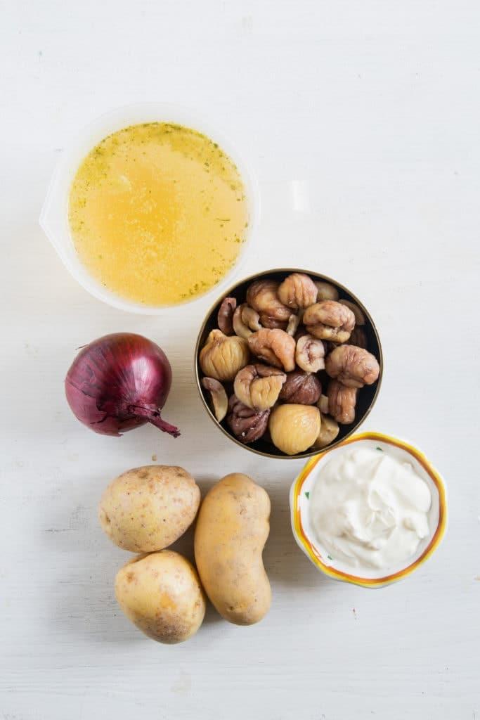 Zutaten für die Maroni-Kartoffelsuppe auf weißem Untergrund. Flatlay.
