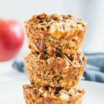 Drei Oatmeal Muffins mit Apfel und Nüssen gestapelt übereinander. Aufnahme von vorne auf Augenhöhe. Sehr viele Details erkennbar.