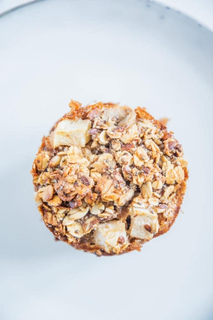 Oberfläche eines Oatmeal Muffins in der Nahaufnahme von oben auf einem blaugrauen Teller.