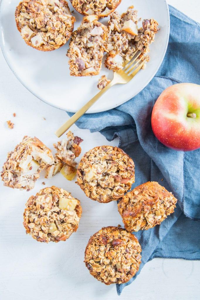Oatmeal Muffins mit Apfel und Nüssen von oben auf weißem Untergrund mit blauem Leinentuch und einem Apfel. Die Oatmeal Muffins sind von oben sichtbar oder liegen auf der Seite. Einer ist auseinander gebrochen.